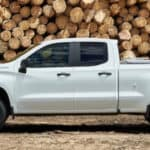2019 Chevrolet Silverado 1500 in white parked in front of a large wood pile
