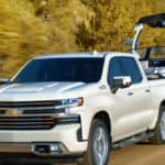 2019 Chevrolet Silverado 1500 in white towing a boat down a hill.