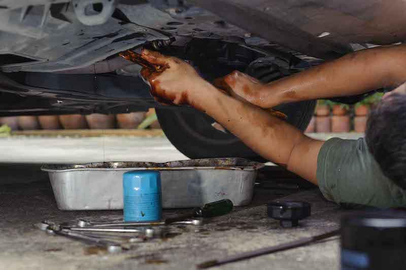 Car Mechanic Loosening Oil Filter Under a Car