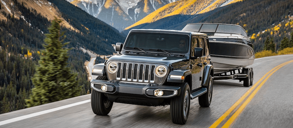 jeep wrangler towing a boat on mountain road