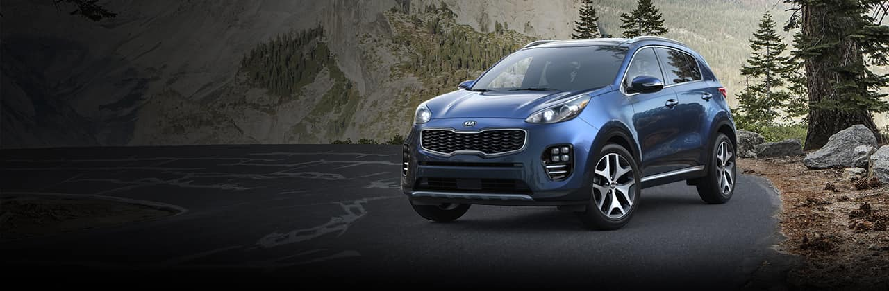 A blue 2018 Kia Sportage on a mountain road
