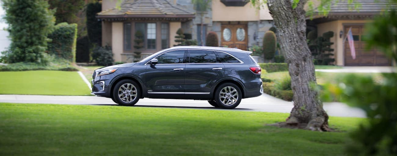 A gray 2019 Kia Sorento driving by an upscale home