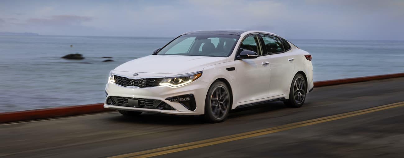 A white 2019 Kia Optima driving along a beach