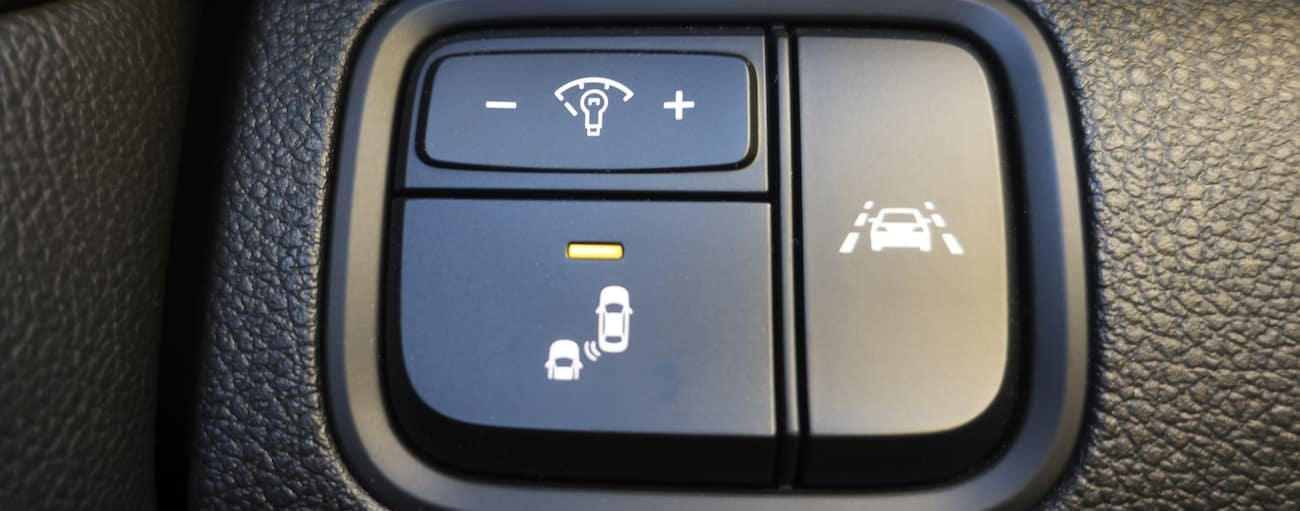A closeup of the driver assist toggle buttons on a 2019 Kia Optima SX