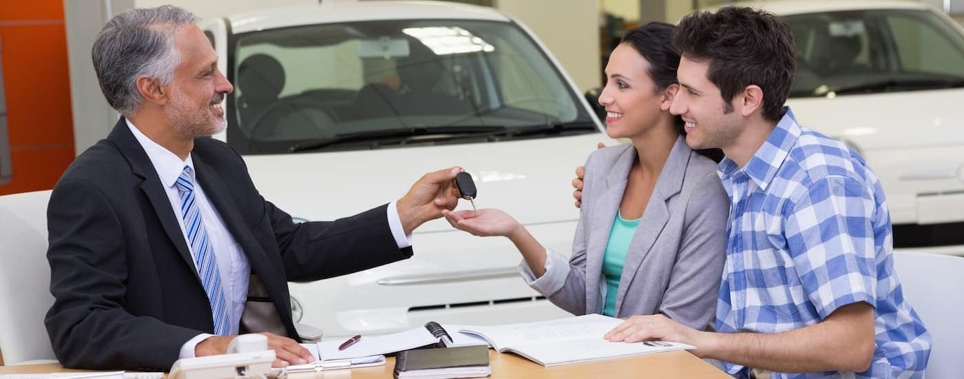 A friendly and knowledgable salesman helps a couple buy a new car at a Kia dealership near you