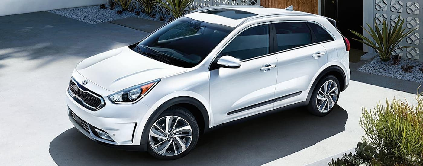 A white 2019 Kia Niro is parked in a driveway after being purchased from a Freehold, NJ Kia dealership.