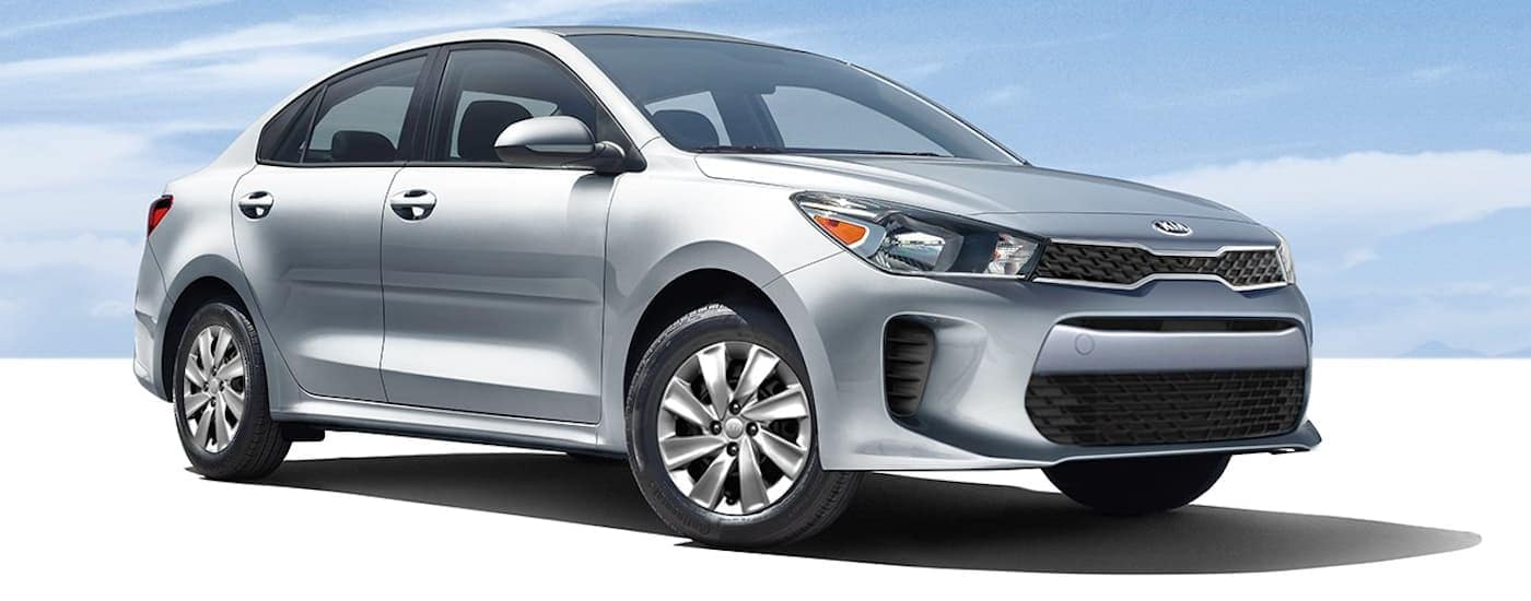 A silver 2019 Kia Rio parked with blue skies was purchased from a Freehold, NJ, Kia Dealership.