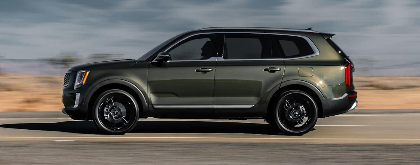 A green 2019 Kia Telluride is on a road in the desert. Find yours at a Kia dealership in Freehold, NJ.