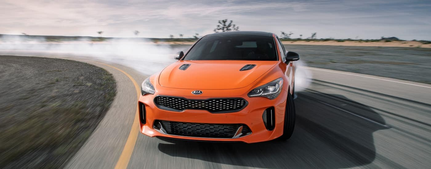 An orange 2020 Kia Stinger is drifting around a racetrack near Freehold, NJ.