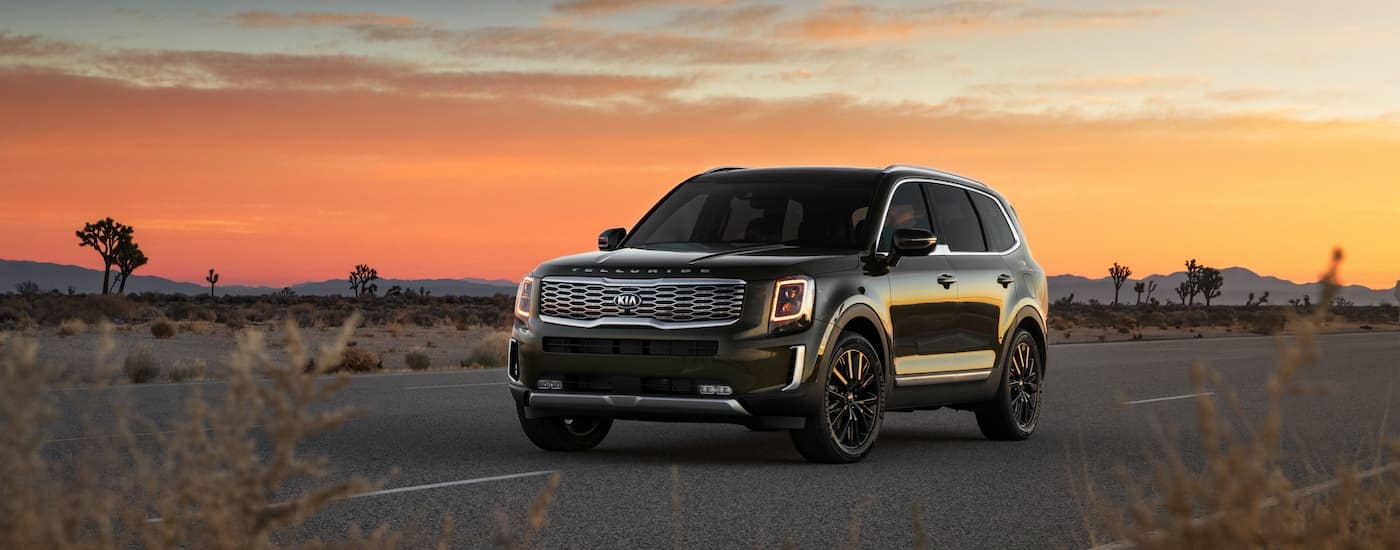 A green 2020 Kia Telluride, which can be ordered from a Kia dealership in NJ, is parked with a sunset behind it near Freehold, NJ.