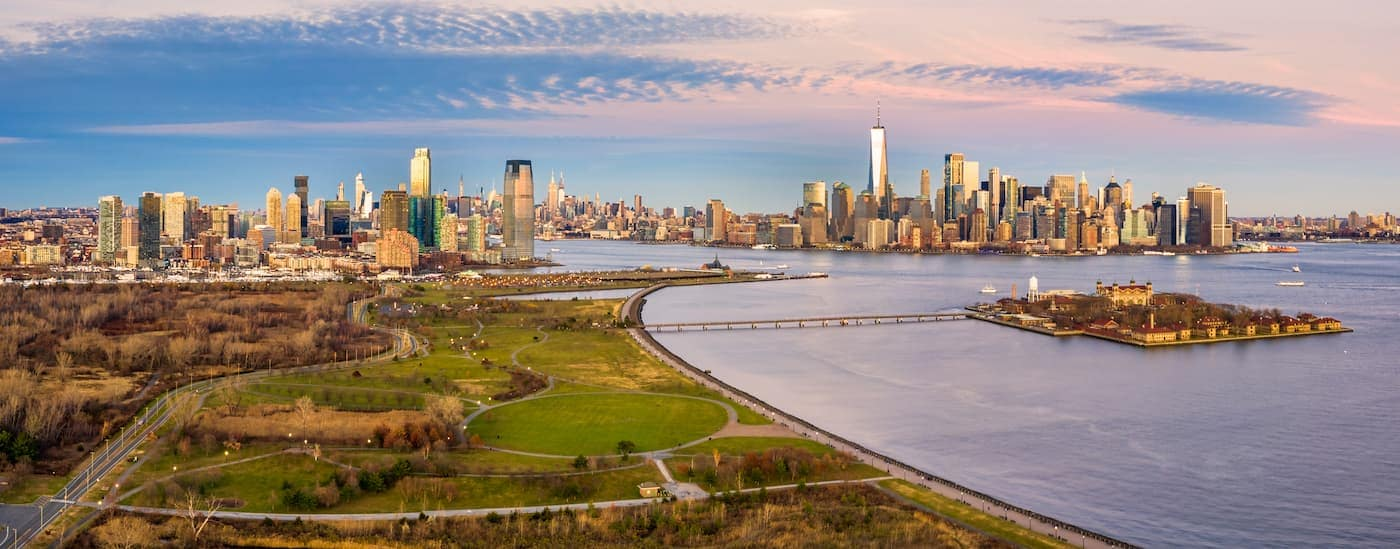 An aerial view of Liberty State Park and Ellis Island are shown with the NY City skyline in the distance.
