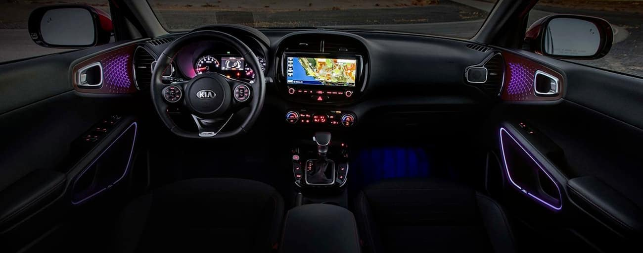 The black interior of a 2020 Kia Soul is shown with purple accents.