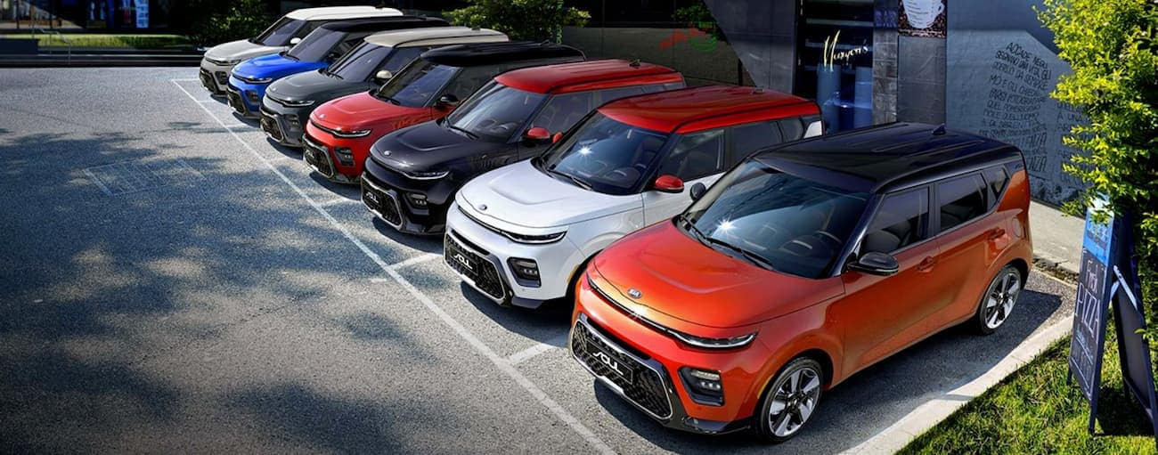 A line of multi-colored 2020 Kia Souls are parked in front of a building.