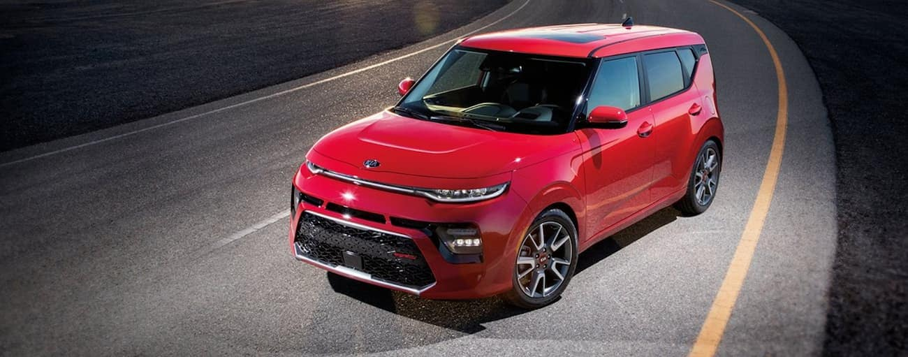 A red 2020 Kia Soul is on a dark road near Freehold, NJ.
