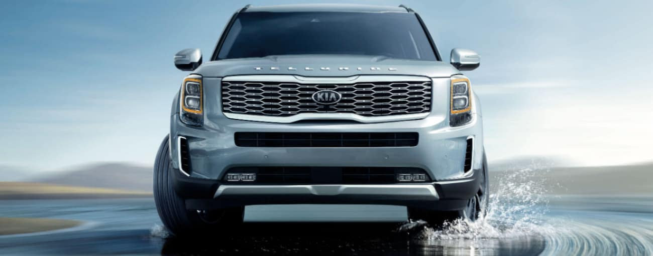 A blue 2020 Kia Telluride is driving on a wet road near Freehold, NJ.