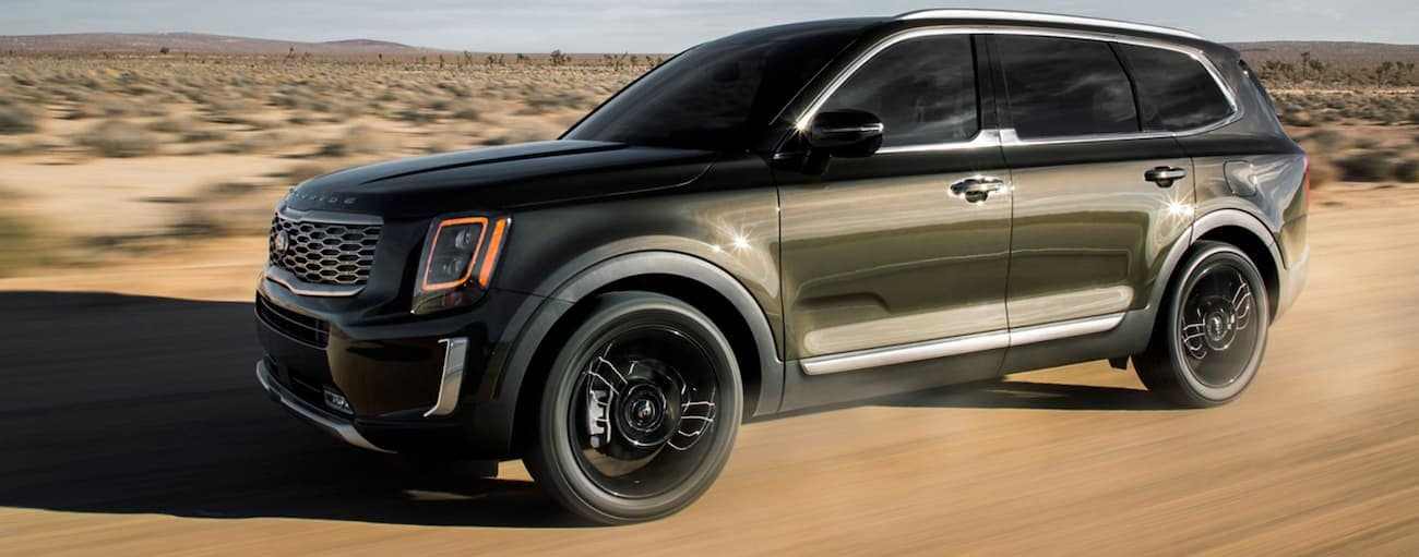A green 2020 Kia Telluride is driving on a desert road.
