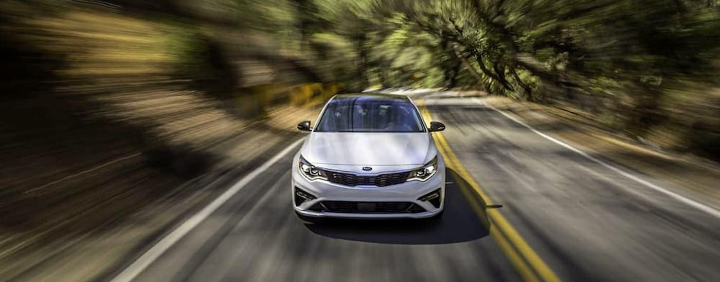 A white 2019 Kia Optima, part of some Kia lease deals, is driving on a backroad.