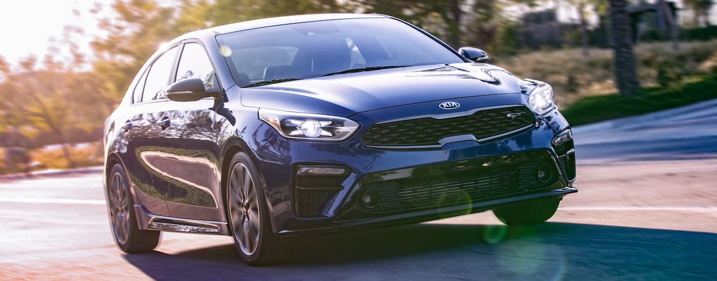 A blue 2020 Kia Forte GT is driving outside Freehold, NJ with sun flares.