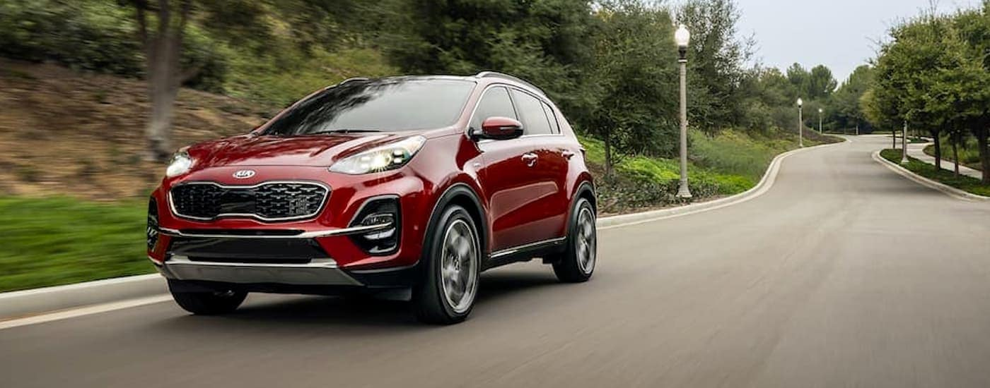 A red 2020 Kia Sportage is driving on a tree-lined street.