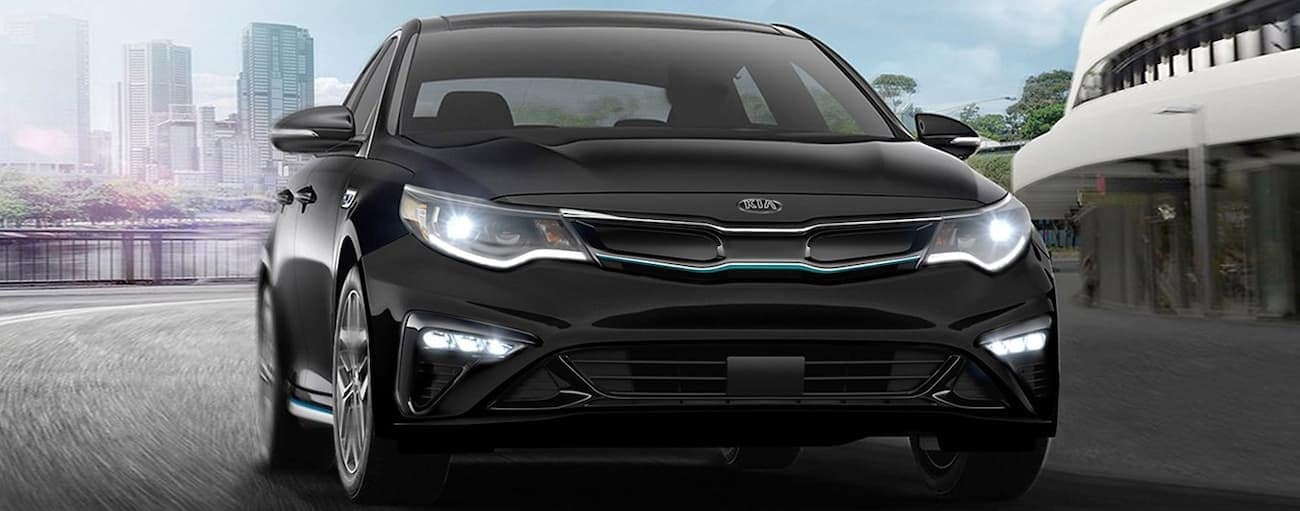 A black 2020 Kia Optima is driving away from a city.