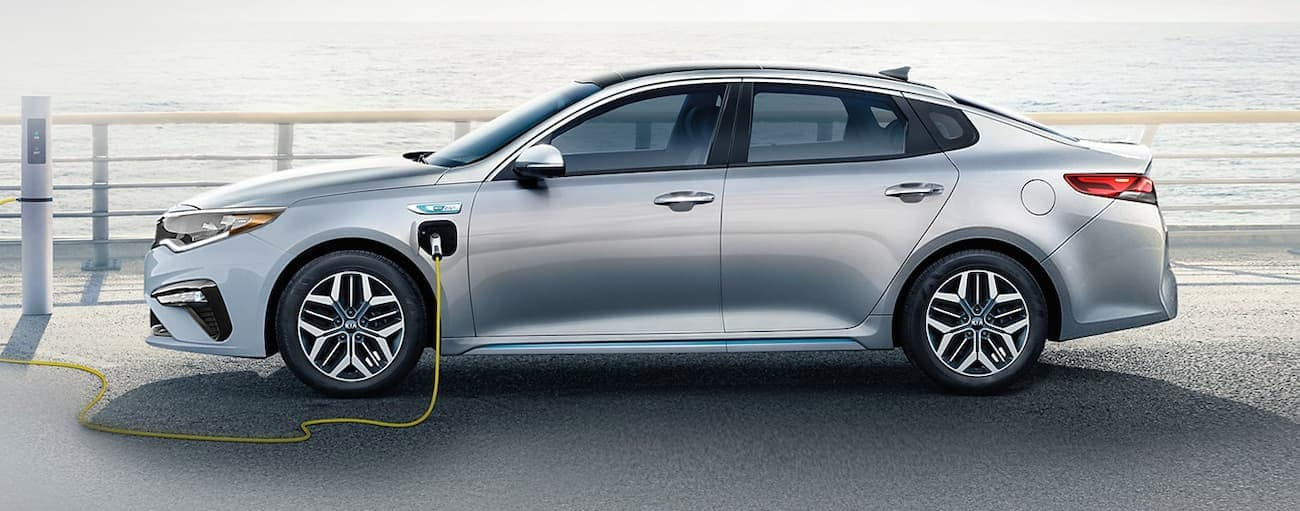 A silver 2020 Kia Optima Plug-In Hybrid is plugged in next to water.