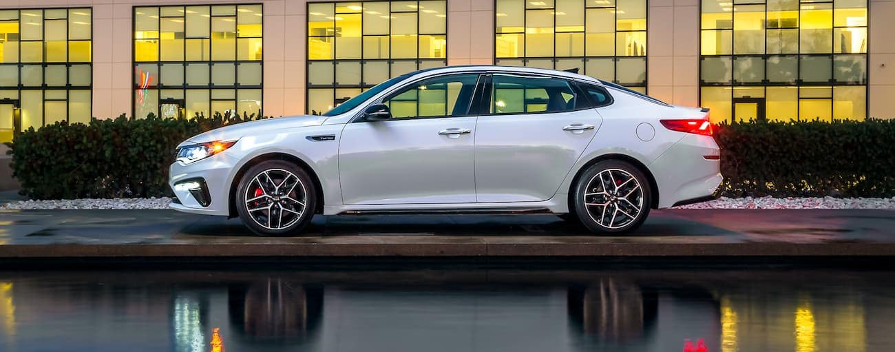 A white 2020 Kia Optima is parked in front of a building with many large windows near Freehold, NJ.