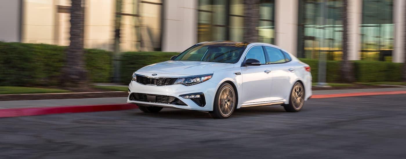 A white 2019 Kia Optima is driving in front of a building with many windows.