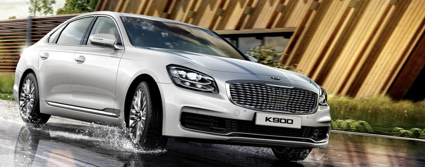 A silver 2019 Kia K900 is driving through a puddle.