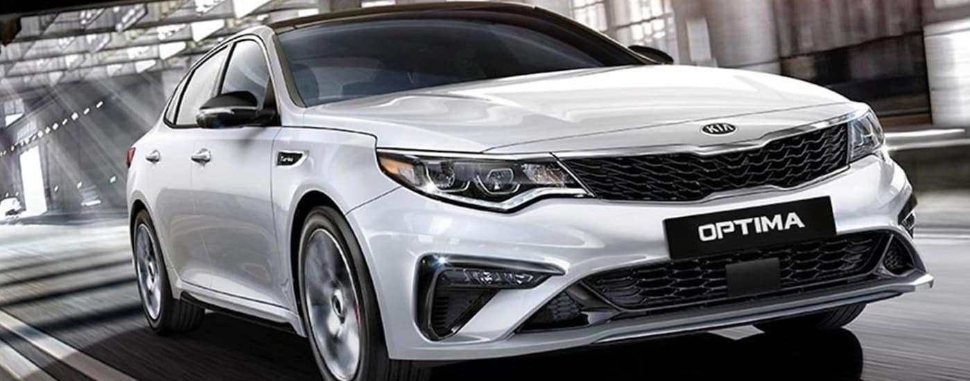 A white 2019 Kia Optima, popular at Kia dealership locations near you, is driving on a highway.