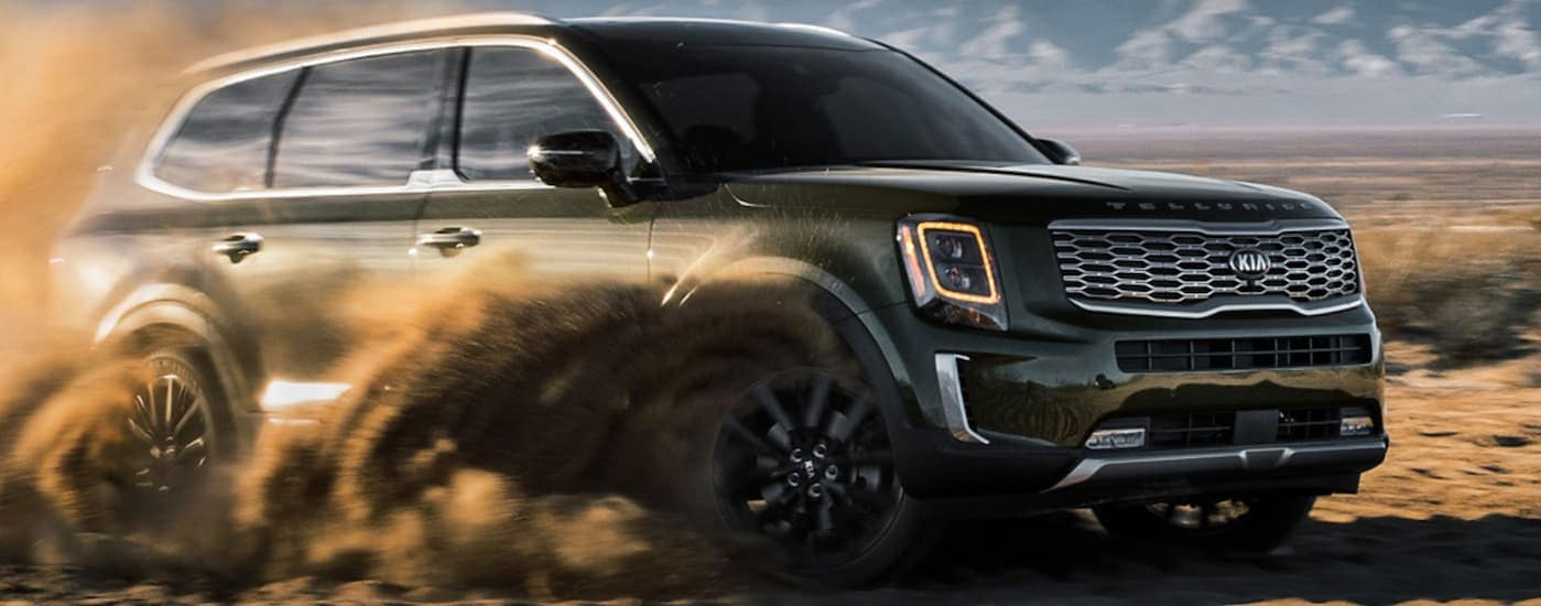 A green 2020 Kia Telluride, after leaving one of many local Kia dealership locations, is driving through dirt.