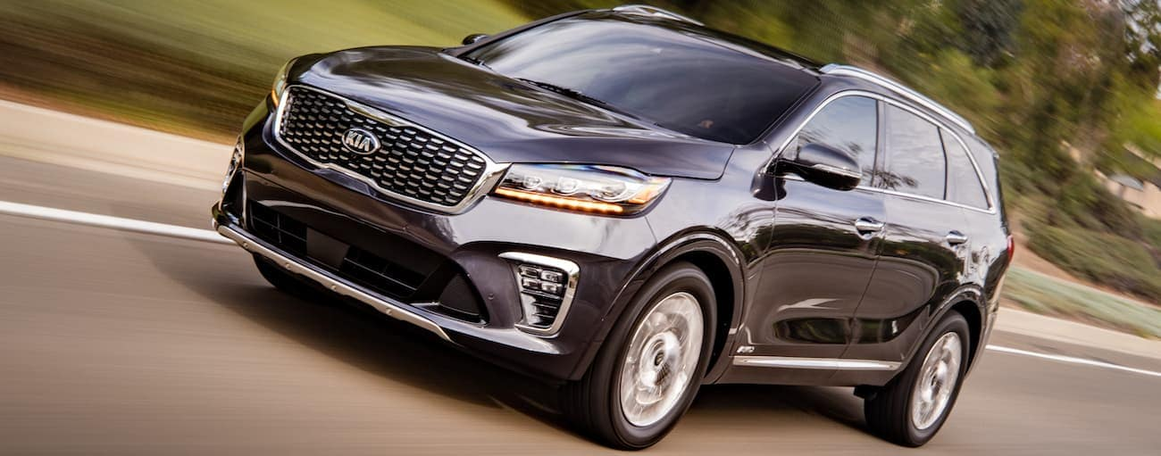 A dark grey 2020 Kia Sorento is driving on a road passing a lawn in Freehold, NJ.