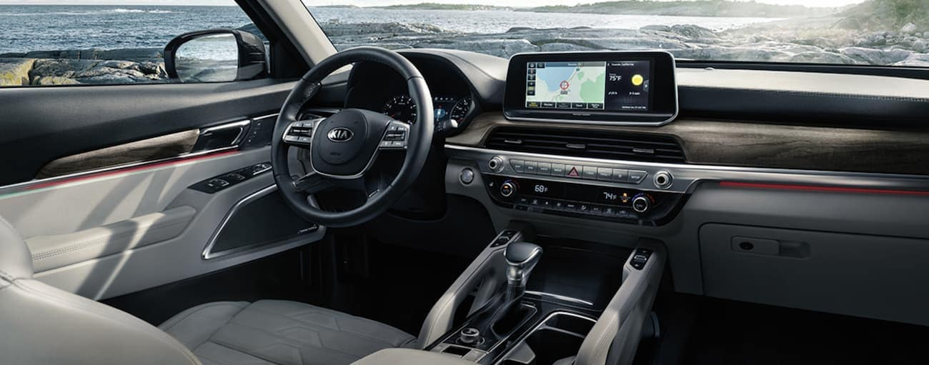 """The front white leather interior of a 2020 Kia Telluride is shown with a  10.25"""" touchscreen display."""