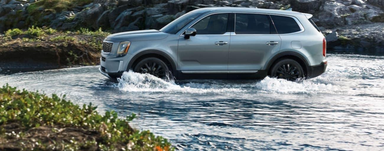 A silver 2020 Kia Telluride is driving through a small river near Freehold, NJ.