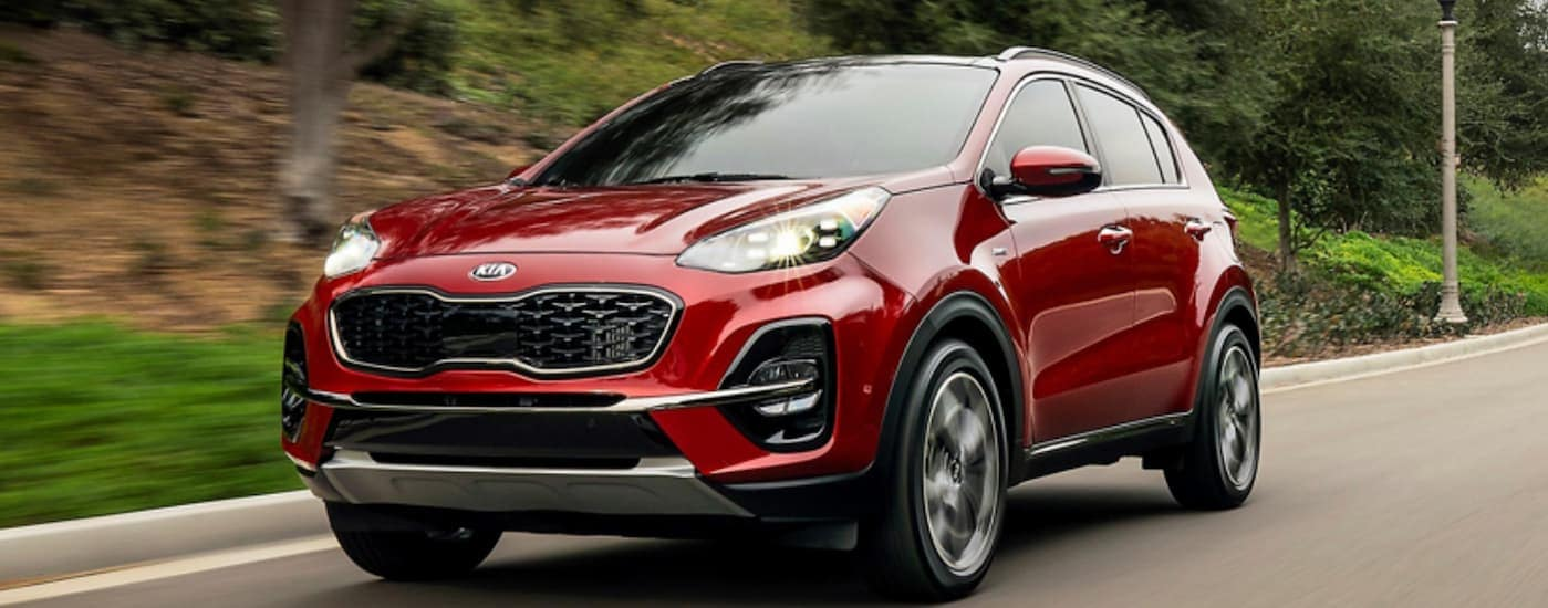 A red 2020 Kia Sportage is driving on a treelined road after leaving a Kia dealership location near Jersey City, NJ.