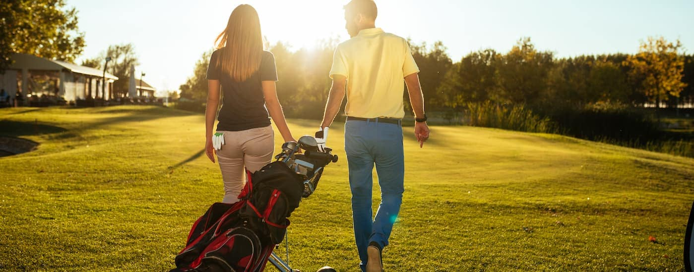 A couple is walking on one of the best local Eatontown Golf Courses on a sunny day.