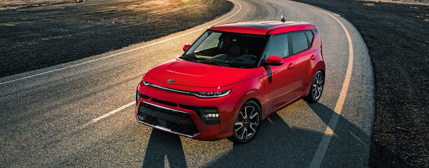 A red 2020 Kia Soul is parked on a road while the sun sets behind it.