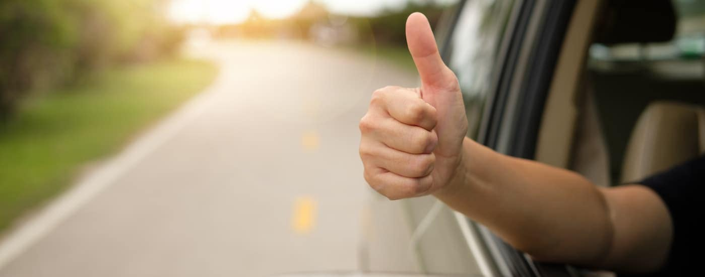 A man has his hand out of the window of a Kia car while giving the thumbs up.