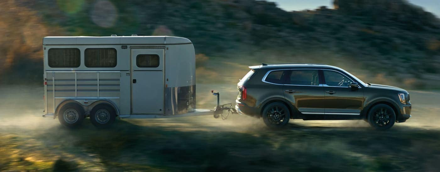 A side view of a green 2020 Kia Telluride is driving on a dirt road while towing a large horse trailer.