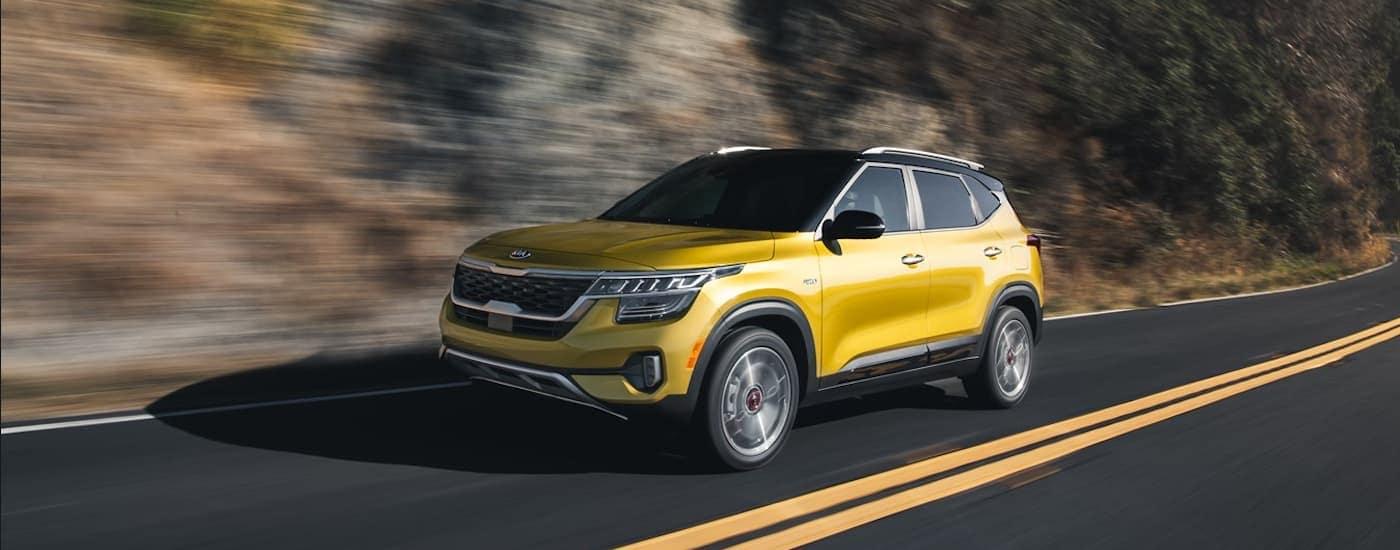 A yellow 2021 Kia Seltos is driving on a treelined road near Freefold, NJ.