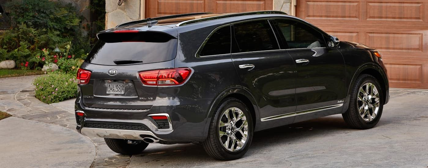 A grey 2020 Kia Sorento is parked in a driveway while facing wooden garage doors.