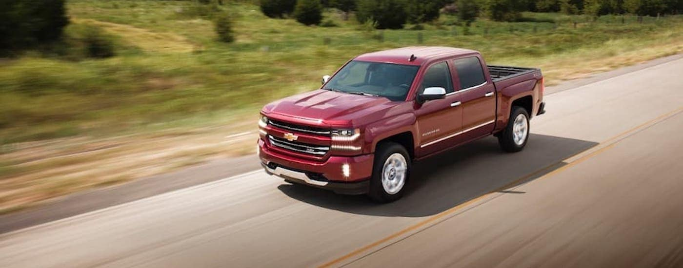 A red 2017 Chevy Silverado is driving on a tree-lined road.