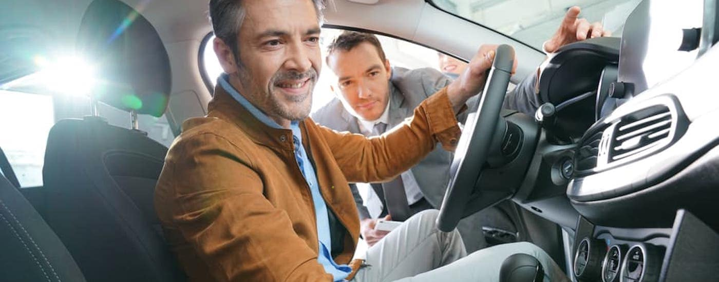 A man is sitting in a used car while the salesman talks to him.