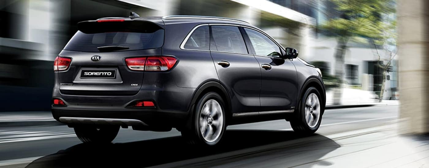 A black 2016 Kia Sorento, which is popular among used cars in Philadelphia, is driving on a city street.