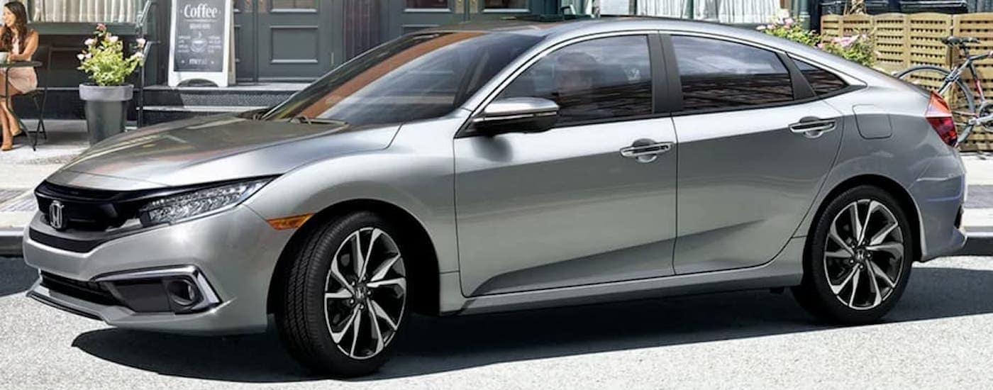 A silver 2019 Honda Civic is backing up into a parking space.