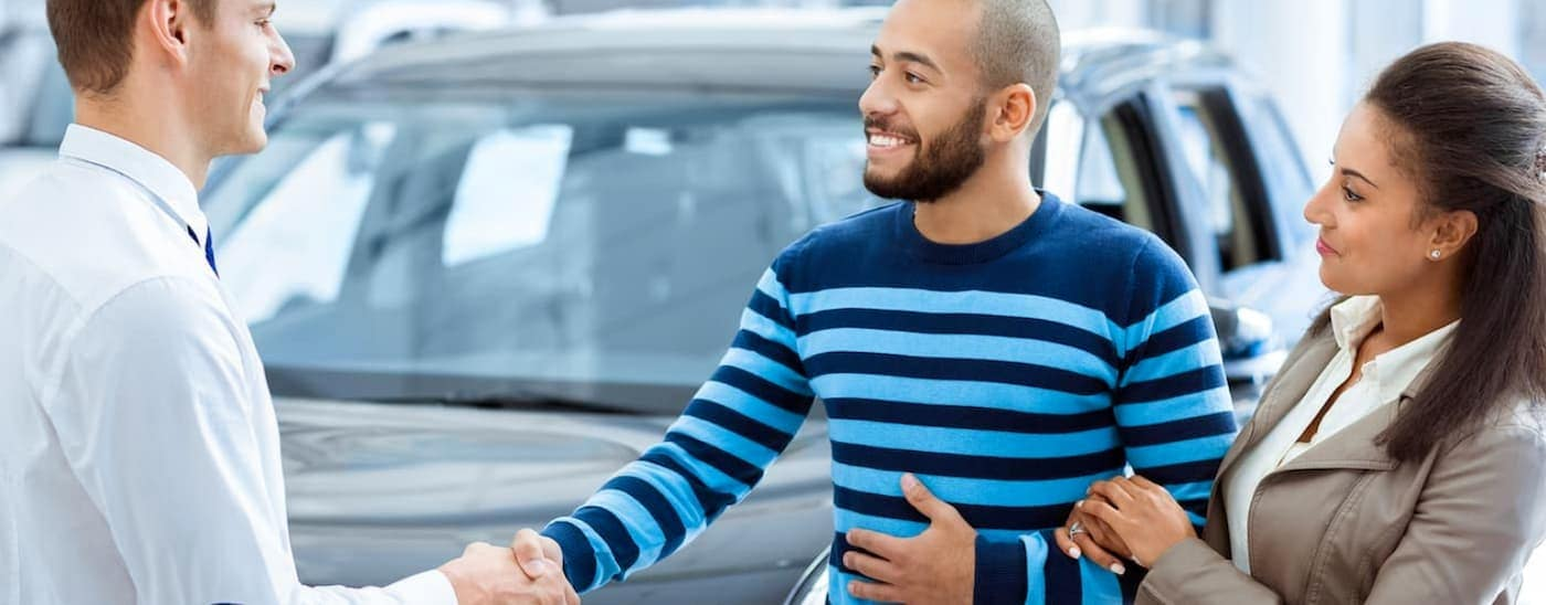 A salesman is shaking hands with a husband who is with his wife in front of used cars.