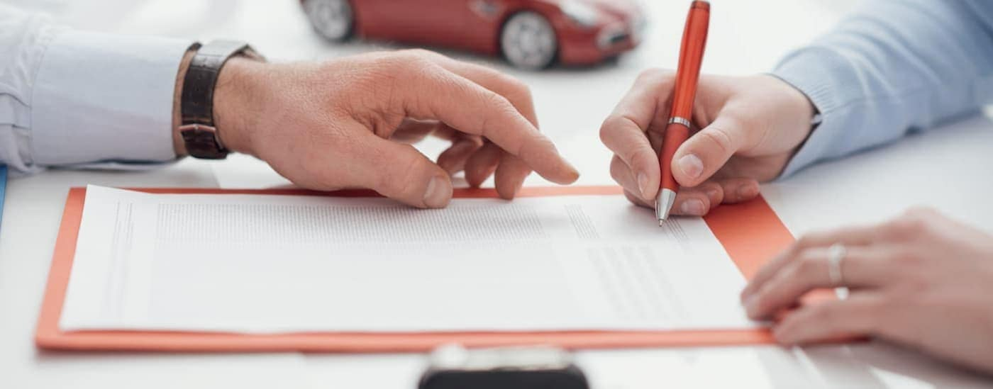 A salesman is pointing to where the buyer needs to sign on a loan.