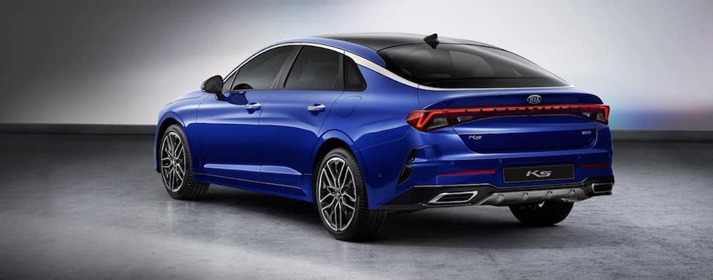 The rear of a blue 2021 Kia Optima is shown in a white room.