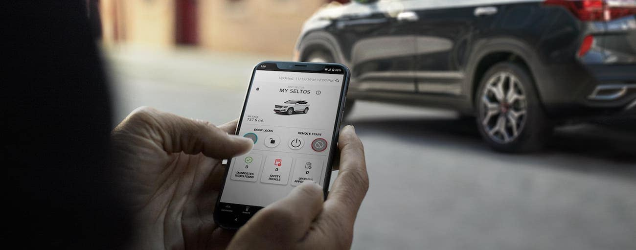 Hands holding a smart phone and controlling features on a gray 2021 Kia Seltos
