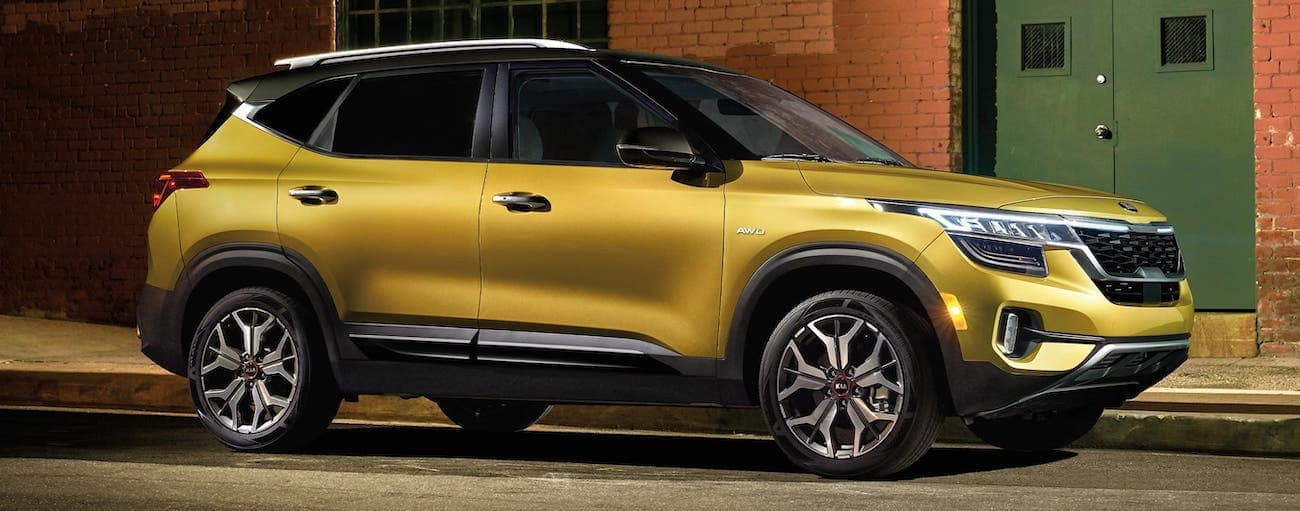 A yellow 2021 Kia Seltos SXT is parked in front of a brick building.