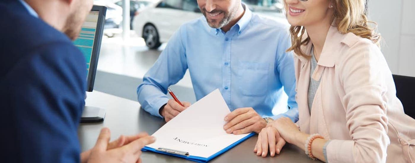 A couple is signing paperwork for a used car at a dealership.